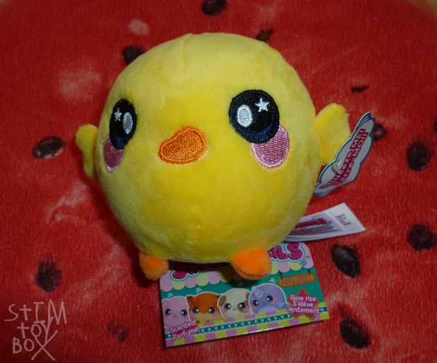"A round, yellow Squishimals toy sitting on a red watermelon slice pillow. The Squishimal is a round ball-shaped plush shaped like a very kawaii-styled chick, with a yellow plush body and wings, small orange feet, and oversized black embroidered eyes with white pupils and star-shaped eye-shines, pink embroidered cheeks under the eyes and an orange embroidered beak in the centre of its face. A white paper tag attached to the wing says ""squeeze me"" in English and French, white product tags are attached to its back and stick out across the underside of its body, and a cardboard swing tag featuring cartoon images of various Squishimals under a colourful header sits underneath the toy."