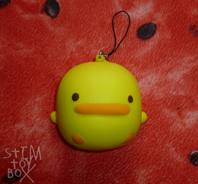 A yellow duck-cake squishy sitting on a red watermelon slice pillow. The squishy is shaped like a squarish cake bun with bright yellow icing, small stubby yellow arms and two orange dots for feet. It has brown dot eyes above a rounded orange rectangle for a beak, resulting in a very stylised duck–how a duck might look were it a cake. A black phone charm strap is attached to a plastic eye pin at the top of the squishy.