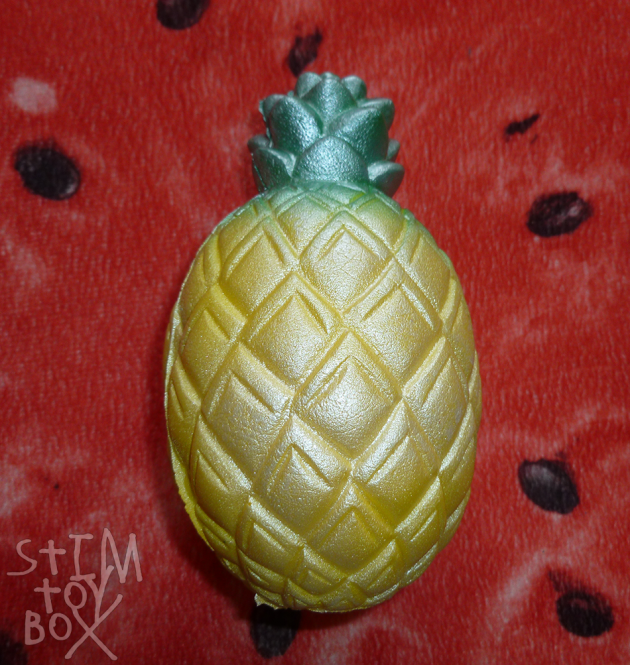 A photo of a pearlescent pineapple squishy sitting on a red watermelon slice pillow. The squishy has a yellow oval-shaped base with a raised diamond-scale pattern to mimic the texture of a real pineapple, finishing with a stem composed of small protruding leaves. The leaves are bright green covered with a pearly green paint, the fruit bright yellow covered with a pearly yellow paint. A few bubbles in the foam are visible under the paint layers.