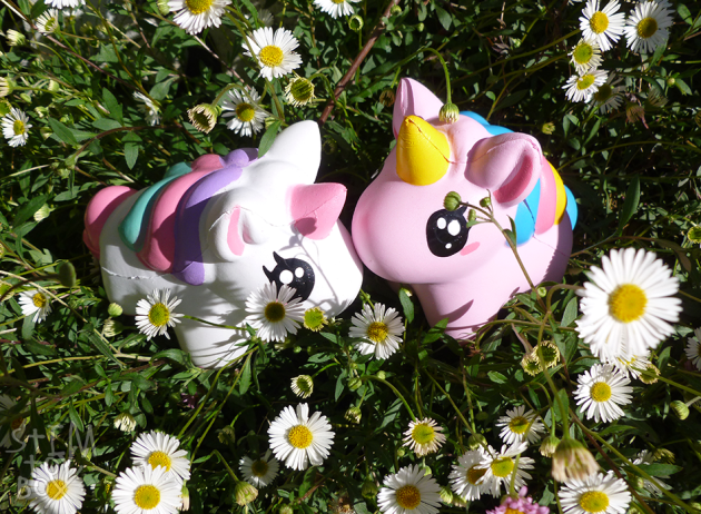 Two plump three-dimensional unicorn squishies sitting in the middle of a pink and white daisy bush. The unicorns are somewhat like vintage My Little Pony with a little more kawaii styling, with oversized eyes, oversized heads and chubby bodies. The squishy on the left is white with a pink tail and horn, with a purple/pink/aqua striped mane. The squishy on the right is pastel pink with a blue tail, a yellow horn and a blue/pink/yellow striped mane. Both have large, round black eyes with three white eye shines, two lashes and a small pink stripe for a cheek. The photo is taken in bright sunlight.