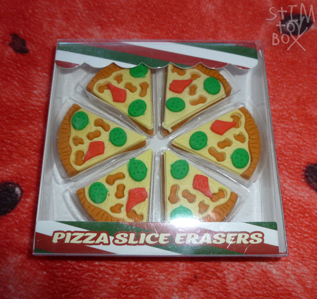 """A set of six pizza slice erasers, sitting on a red watermelon slice pillow. The pizza slices are cut into triangles with a curved out edge, together forming a circle, and have a tan brown crust and base, a light yellow cheese layer fitting into grooves in the crust, two round green pieces with indented dots that fit into the cheese layer, and a red grooved wing-shaped piece. The effect mimics chopped-up vegetables and meat atop a pizza. The erasers sit in a clear plastic shell in a cardboard box with a green/maroon/white striped trim at the top and bottom. Text at the bottom in maroon-outlined cream type reads """"pizza slice erasers""""."""